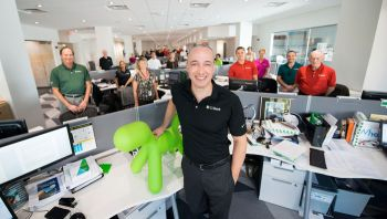 CEO's space is like everyone else's at C1 Bank. Green dog statues, bought as a toy for Trevor Burgess's young daughter, are now in every location.